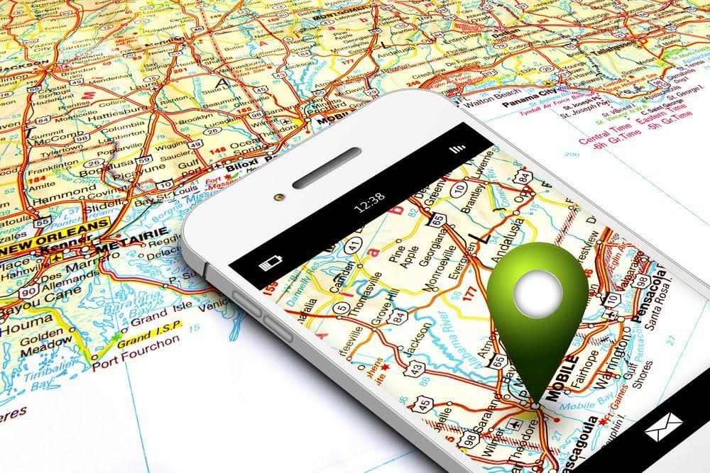 mobile phone with gps laying on map background